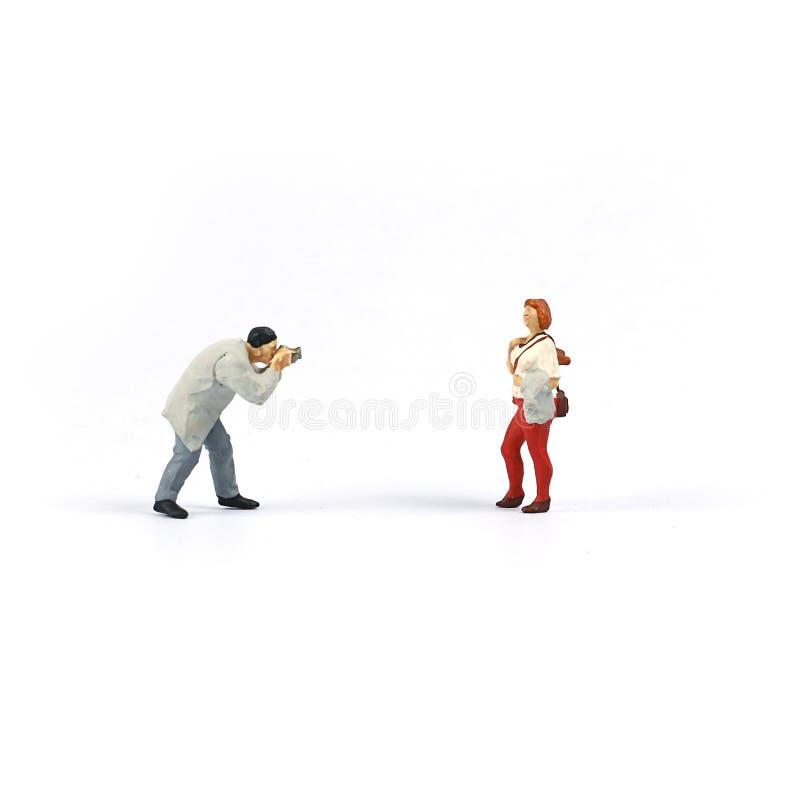 微型图人们,拍女孩的一张照片的摄影师 免版税图库摄影