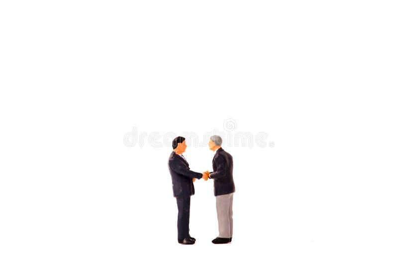 微型图商人握手在白色背景 免版税图库摄影