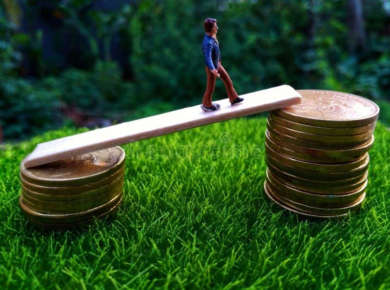 微型图年轻bussinesman早晨继续设法得到走在堆的高收入硬币在新鲜的绿草 免版税库存照片