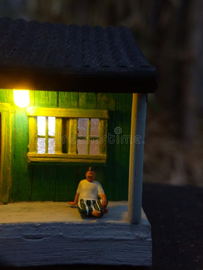 微型图玩具印度尼西亚妇女清洗大阳台和老人的使用sarung,kopiah和白色衬衫,在他的房子坐,以远 免版税库存照片