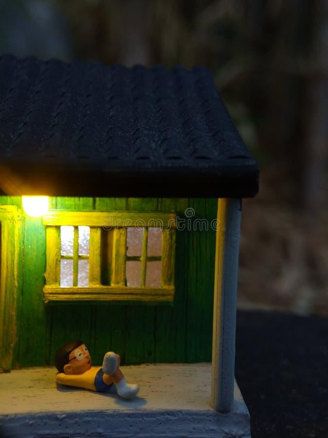 微型图玩具印度尼西亚妇女清洗大阳台和老人的使用sarung,kopiah和白色衬衫,在他的房子坐,以远 库存照片