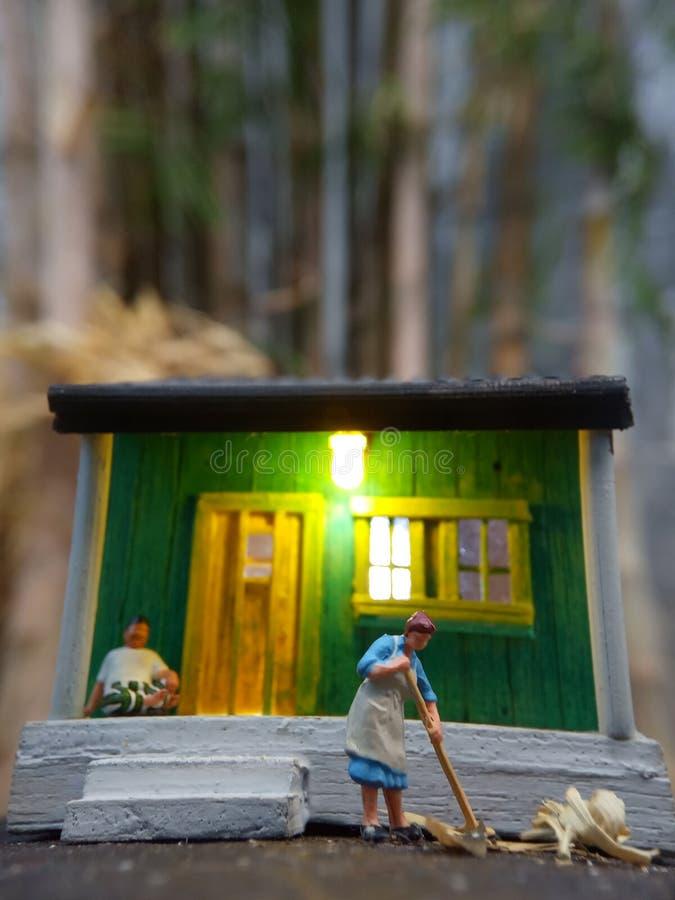 微型图玩具印度尼西亚妇女清洗大阳台和老人的使用sarung,kopiah和白色衬衫,在他的房子坐,以远 免版税库存图片