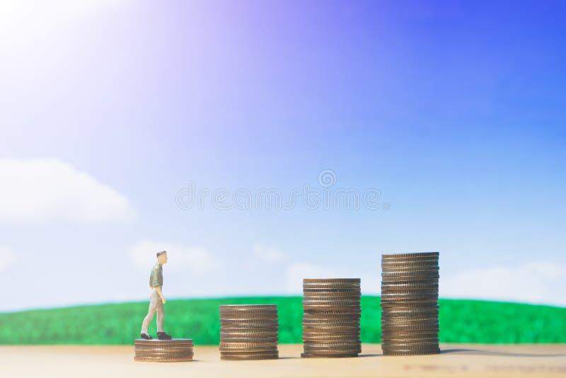 微型在硬币堆金钱的人民小形象走的商人提高在蓝天和白色云彩的生长成长 免版税库存图片