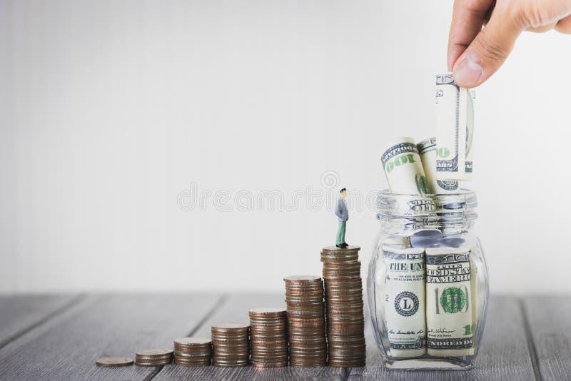 微型在硬币金钱堆的人民小形象立场提高生长成长挽救金钱用投入一百美元的手 免版税库存照片
