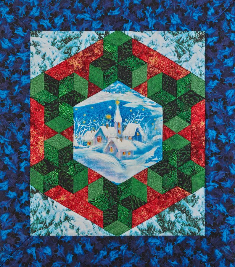 微型大奖章被子一个风格化圣诞节花圈包围的下雪的村庄 库存例证