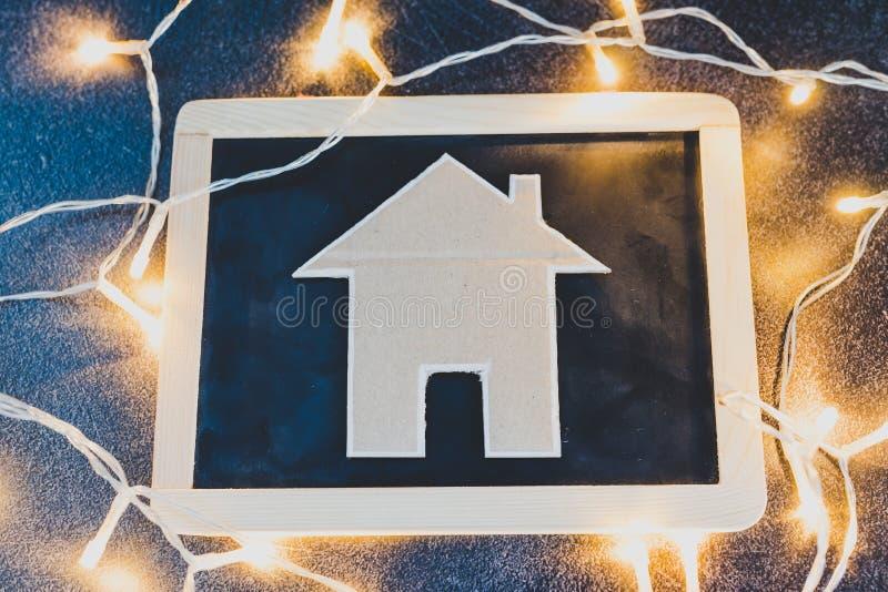 微型房子由纸板制成在黑板和用彩色小灯 库存图片