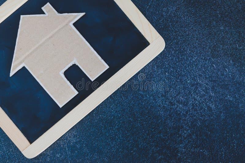 微型房子由纸板制成在黑板和用copyspace增加您的文本 库存照片