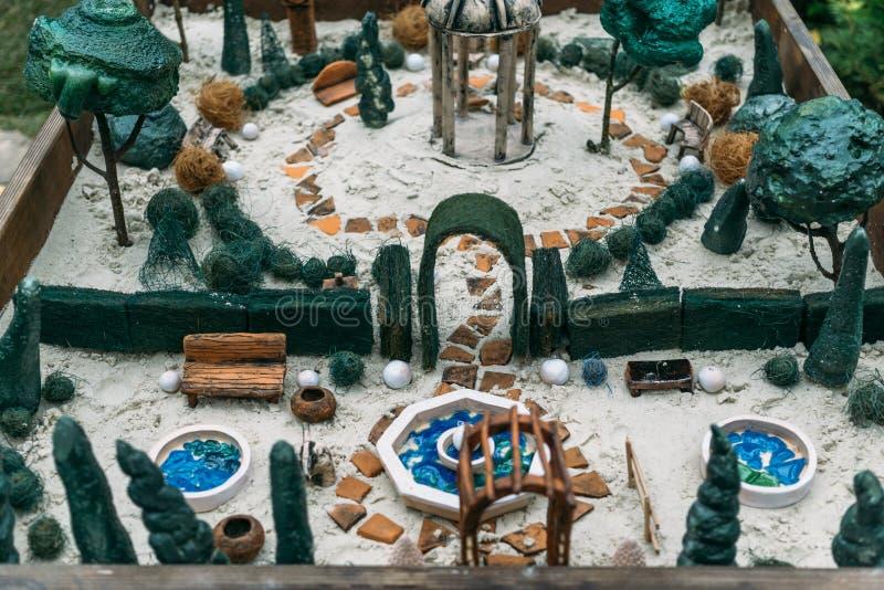 微型房子,玩具风景在沙子箱子反对 免版税库存照片