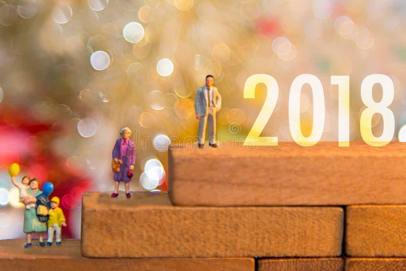 微型拿着气球的小组愉快的家庭站立在木2018年与党新年好 免版税库存照片