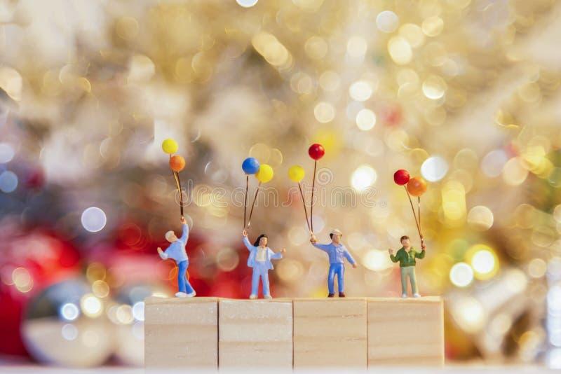 微型拿着气球的小组愉快的家庭站立在木 免版税库存图片