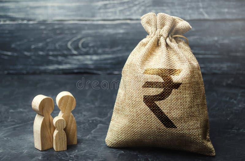 微型木家庭小雕象在金钱袋子附近站立 储款的概念 预算计划 家庭收入 ??  库存照片