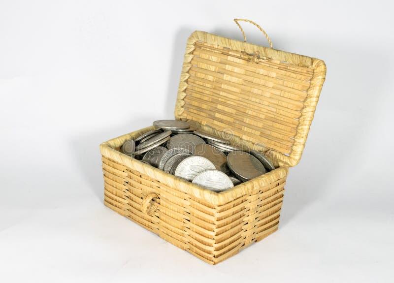 微型柳条胸口填装了用在白色背景的不同的硬币,保存金钱概念 免版税库存照片