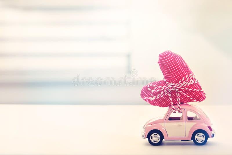 微型桃红色汽车运载的心脏坐垫 免版税图库摄影