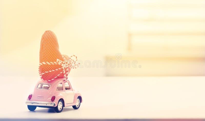 微型桃红色汽车运载的心脏坐垫 库存图片