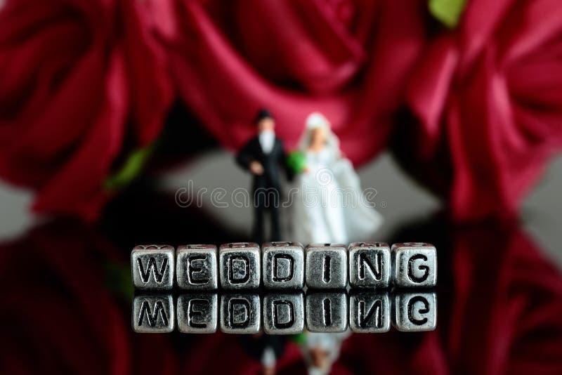 微型比例模型婚礼加上在小珠和玫瑰色花束的词婚礼 库存照片