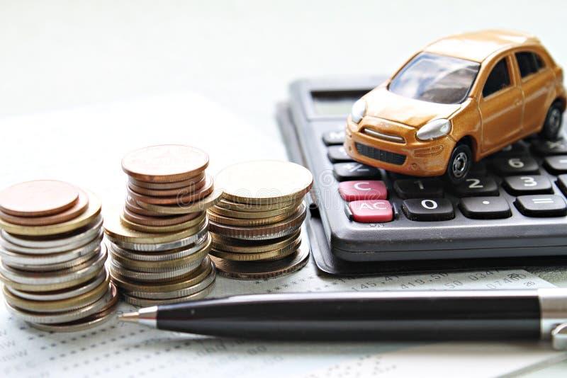 微型汽车模型、硬币堆、计算器和储蓄存款书或者财政决算在办公桌桌上 免版税图库摄影