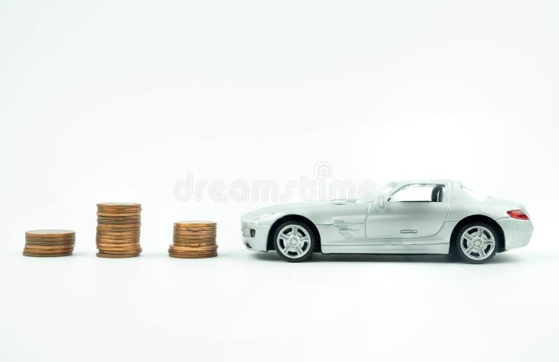 微型汽车模型和硬币塔在白色背景,购买的 库存照片