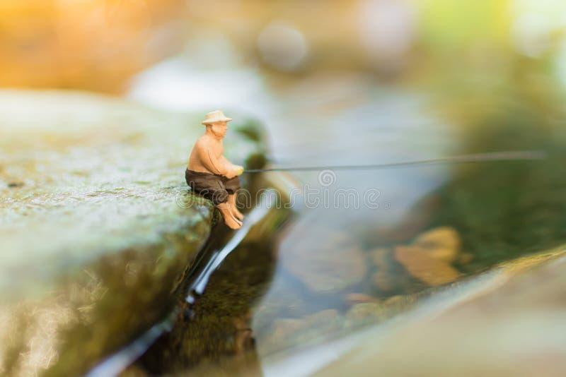 微型渔夫坐石头,钓鱼在河 宏观看法照片,用途作为渔事业概念 免版税库存图片