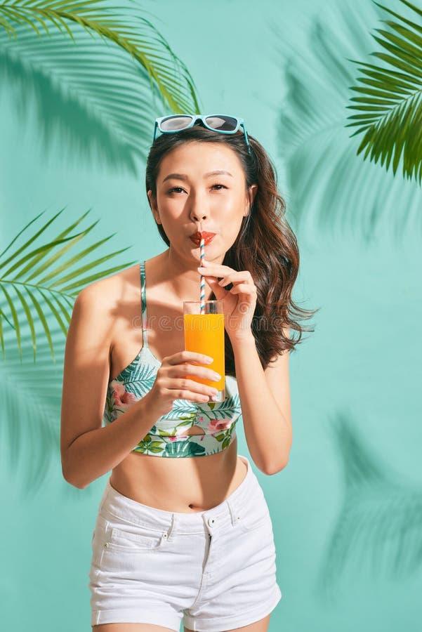 微型牛仔布短裤的年轻性感的亚裔妇女喝在夏时的鲜美汁液 免版税库存照片