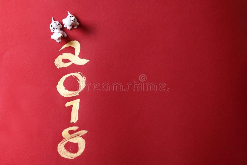 微型狗与在红色表面上的金子2018绘的年 免版税库存照片