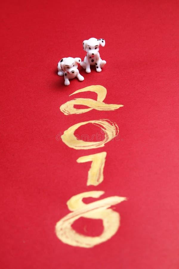 微型狗与在红色表面-系列5上的金子2018绘的年 免版税库存图片