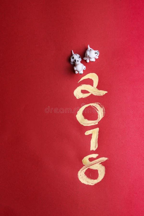 微型狗与在红色表面-系列4上的金子2018绘的年 免版税库存照片