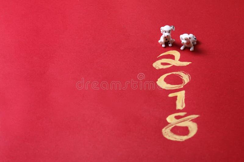 微型狗与在红色表面-系列2上的金子2018绘的年 图库摄影