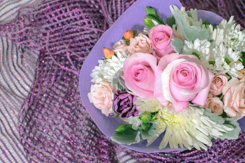 微型玫瑰俏丽的花束在紫色围巾的 图库摄影