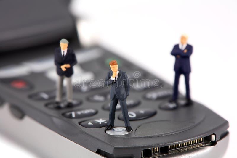 微型生意人的移动电话 库存图片