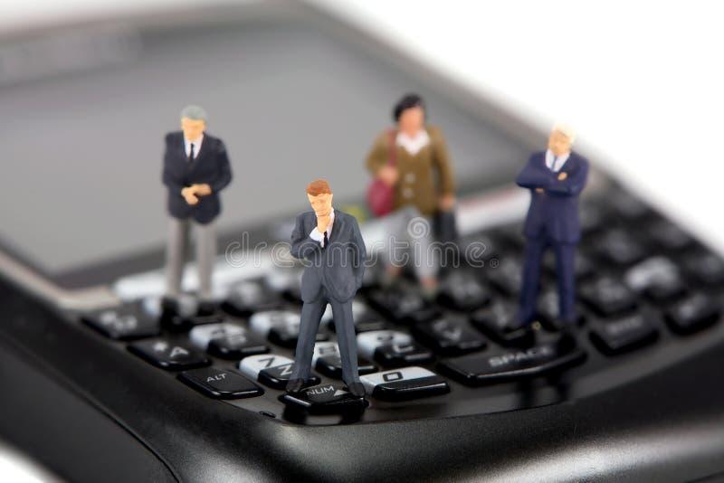 微型生意人的移动电话 免版税库存照片