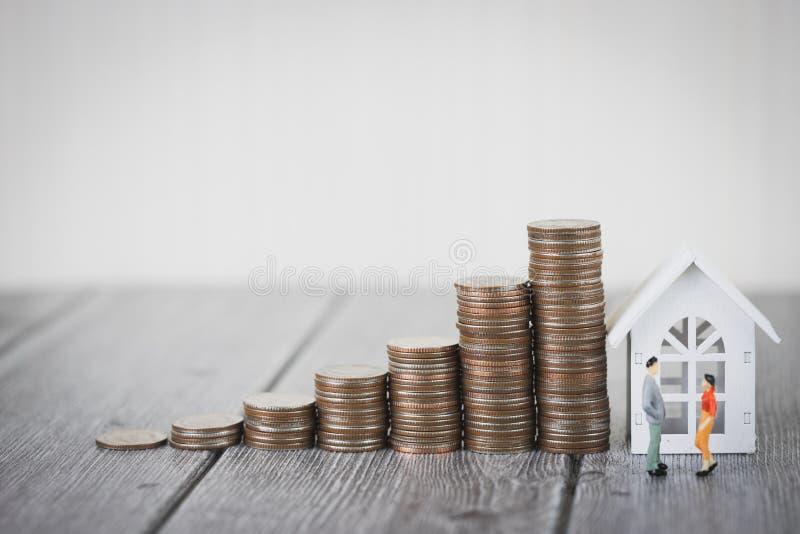 微型站立人民小的形象在硬币金钱堆提高与式样白色房子的生长成长, 免版税库存照片