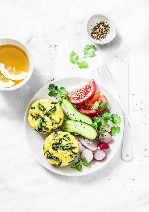 微型菠菜切达乳酪菜肉馅煎蛋饼、菜沙拉和绿茶在轻的背景,顶视图 早餐桌 库存照片
