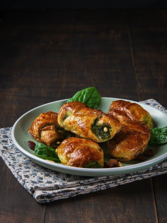 微型菠菜新月形面包用葡萄干、鸟翼末端和山羊乳干酪和与一碗在板材的菠菜有黑暗的背景 库存图片