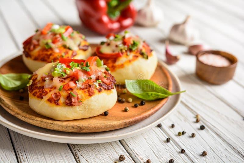 微型薄饼小圆面包用火腿、甜椒、葱和乳酪 库存照片