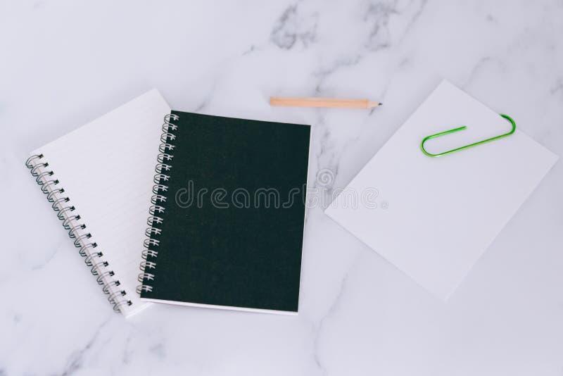 微型螺纹笔记本Flatlay在大理石书桌上的 库存照片