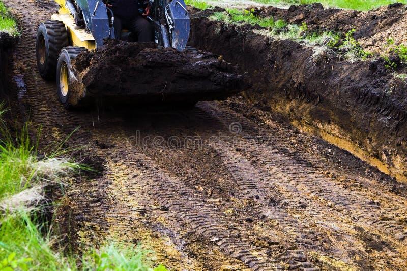 微型装载者播种的看法在基础坑的与在它的桶的地面 免版税库存照片