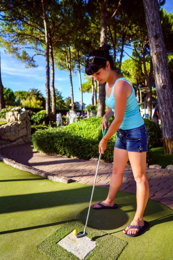 微型高尔夫球-打在绿草的妇女高尔夫球在日落 库存图片