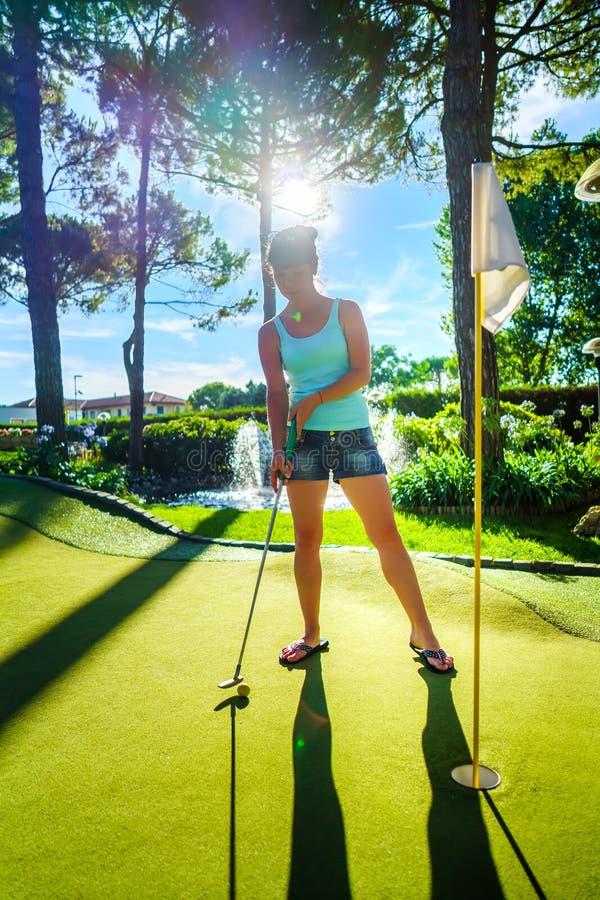 微型高尔夫球-打在绿草的妇女高尔夫球在日落 免版税库存照片