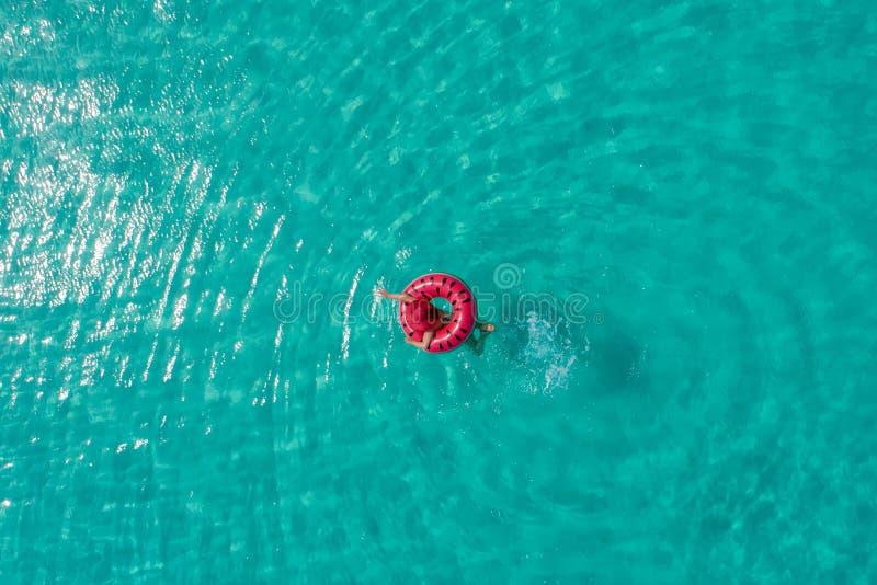 微小的妇女游泳鸟瞰图在游泳圆环多福饼的在透明绿松石海在塞舌尔 夏天海景与 库存照片