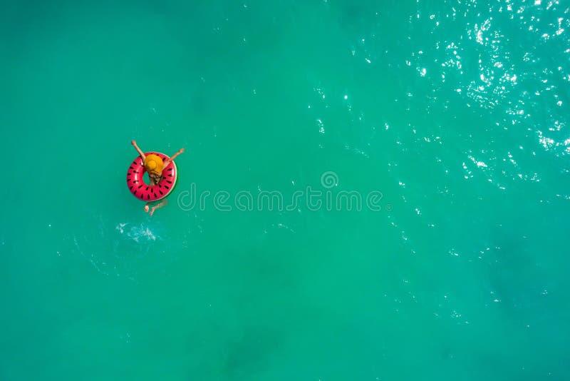 微小的妇女游泳鸟瞰图在游泳圆环多福饼的在透明绿松石海 与女孩的夏天海景,美丽 库存图片