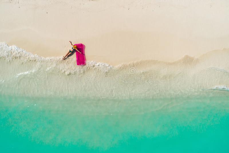 微小的妇女游泳鸟瞰图在游泳床垫的在透明绿松石海 与女孩的夏天海景,美丽 库存照片