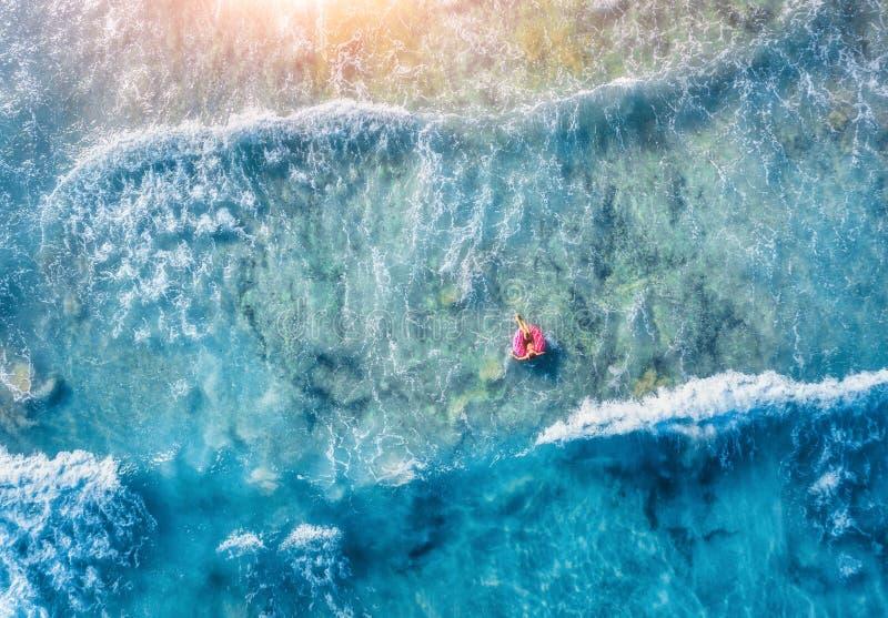 微小的少妇游泳鸟瞰图在多福饼游泳圆环的 免版税库存照片