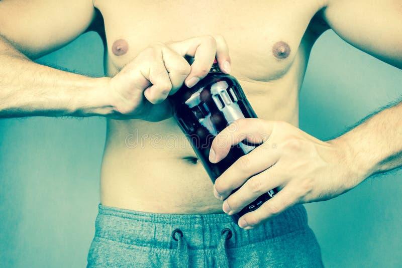 微弱的年轻人打开一个酸樱桃瓶子 免版税库存照片