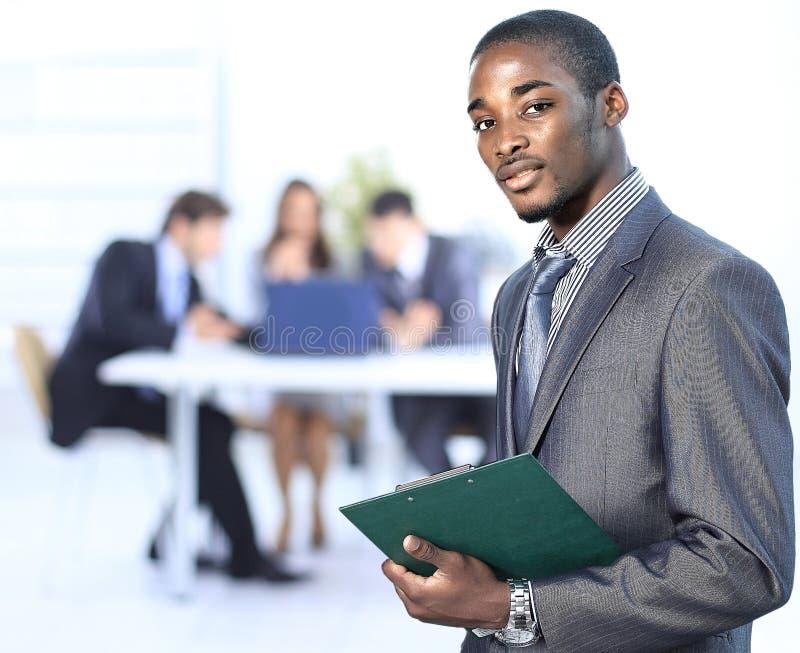 微笑一个成功的美国非洲的商人的画象带领他的队 免版税库存图片