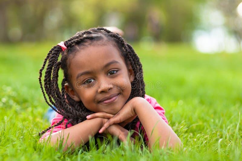微笑一个逗人喜爱的年轻黑人的女孩的室外画象-非洲pe 免版税库存图片