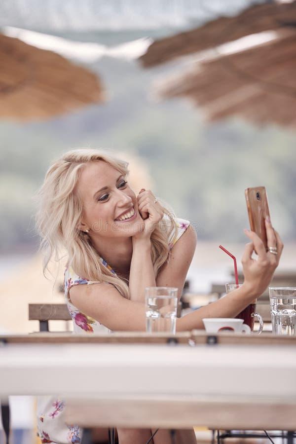 微笑一名年轻美丽的妇女, 25岁,智能手机selfie自画象,坐在海滩咖啡馆,夏天遮光罩 库存图片