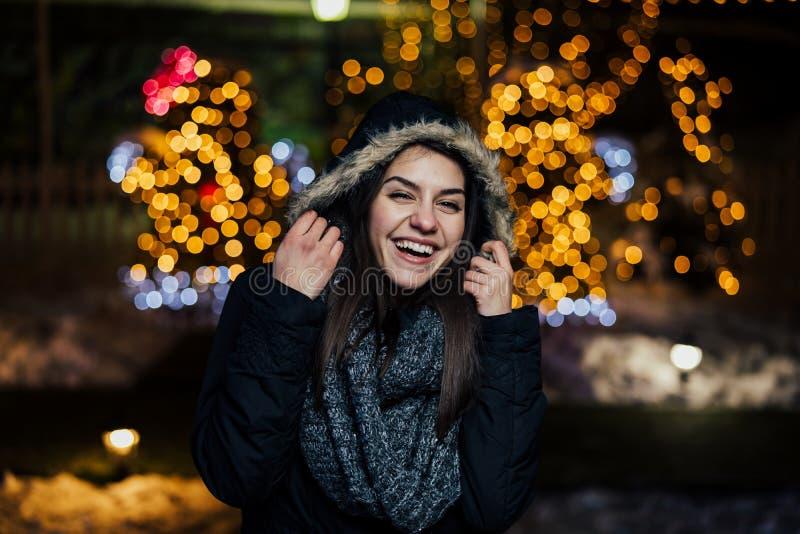 微笑一名美丽的愉快的妇女的夜画象享受冬天和雪户外 冬天喜悦 男孩节假日位置雪冬天 正的情感 免版税图库摄影