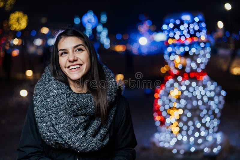 微笑一名gougeous深色的妇女的夜画象享受与雪人的冬天 冬天喜悦 正的情感 幸福 免版税库存照片