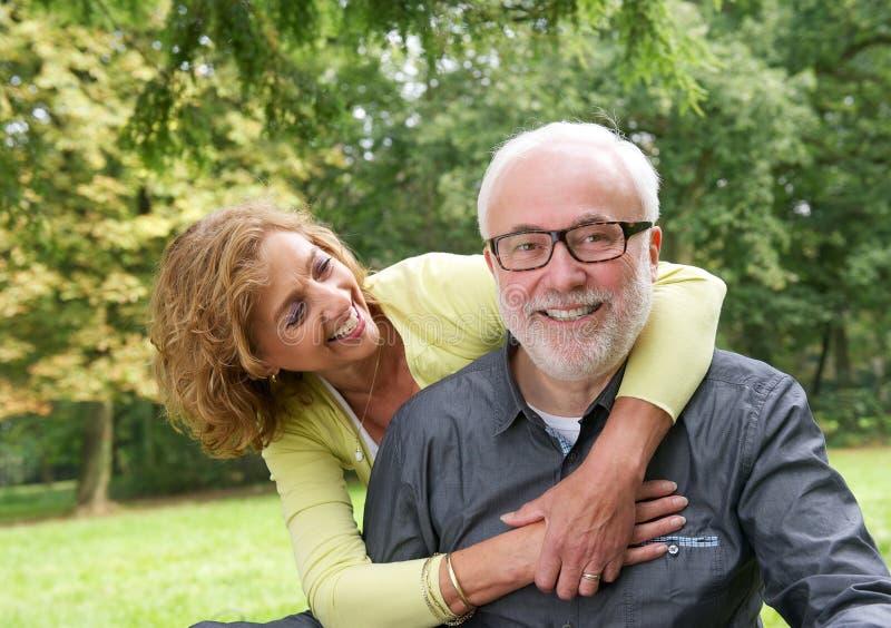 微笑一对有吸引力的更旧的夫妇的画象户外 免版税库存照片