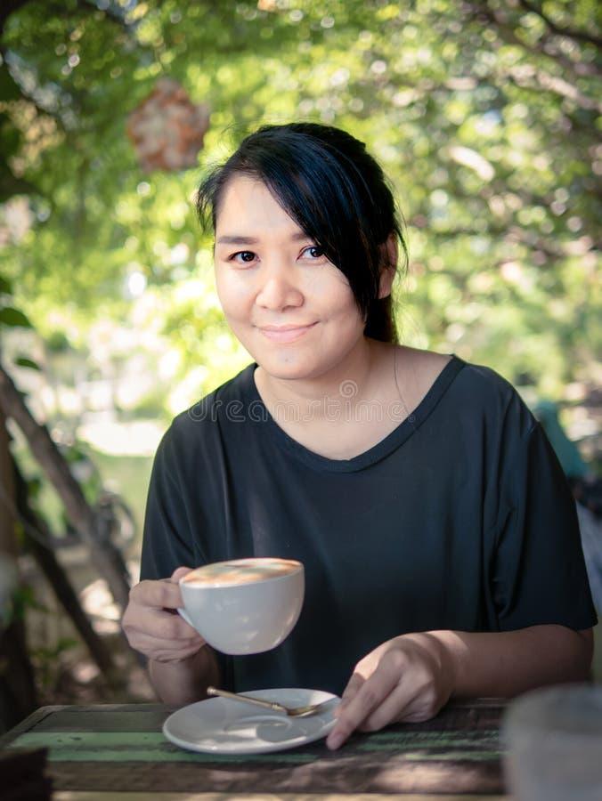 微笑与一个杯子的妇女画象热的热奶咖啡 免版税库存照片